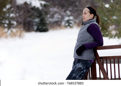 Sporty fit woman in winter running clothing relaxes along nature trail