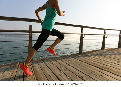sporty fitness female runner running on seaside boardwalk during sunrise