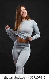 Sporty fitness shape garments concept. Attractive lady in thermal clothes. Young seductive girl pulling shirt showing skin presenting thermoactive clothing on black