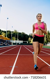 Sporty fitness woman jogging on red running track in stadium. Training summer outdoors on running track line with green trees on background.