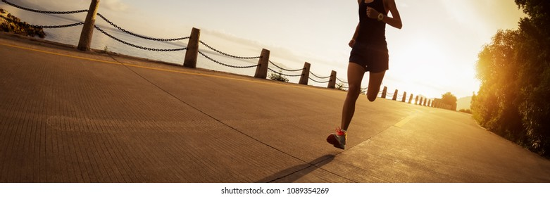 Sporty fitness woman running on sunrise seaside trail