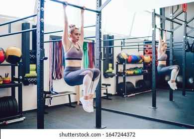Sporty focused female in sportswear with raised legs doing workout exercise hanging on horizontal bar working on abdomen muscles in gym
