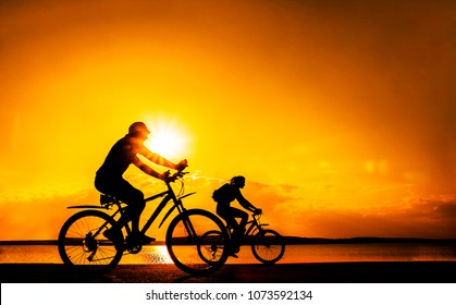 Sporty friends on bicycle on sunset. Silhouette couple cyclist go along coast. Sport in Nature background. Group of people two mountain biker in sunrise with reflection sun in water.Empty Space