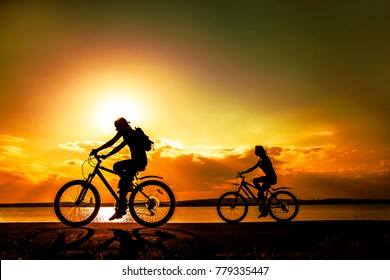 Sporty friends on bicycle on sunset. Silhouette couple cyclist go along coast. Sport in Nature background. Group of people two mountain biker in sunrise with reflection sun in water. Empty Space.