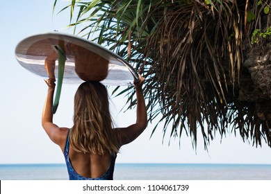 Sporty girl in bikini with surf board walk along dark sea cliff. Young surfer woman run by black sand beach. Active people in sports adventure camp, extreme water activity on summer family vacation