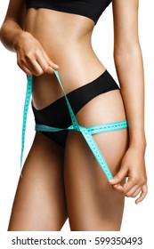Sporty girl in black lingerie with tape measures the size of their hips. Beautiful part of female body. Fitness or body care concept