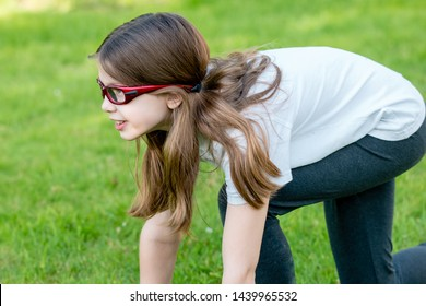 A sporty girl child wearing red prescription sports glasses or goggles participating in athletics - crouch sprint start