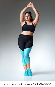 Sporty girl with curvy figure in fashionable sportswear on grey background. Strength and motivation