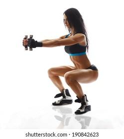 sporty girl doing exercise with dumbbells, silhouette back lit studio shot over white background