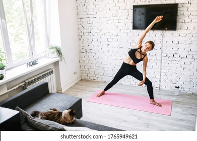 Sporty girl is doing morning exercises. She stands on a mat doing side stretching moves. A long shot of a fit young woman at home, good habits