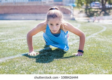 Sporty girl doing push up front view on sports field looking up at camera, focused.
