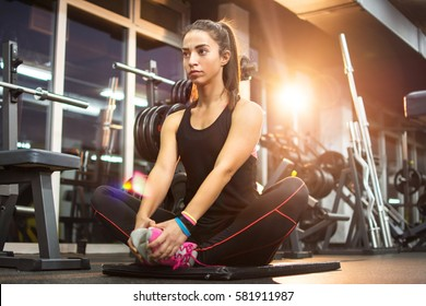 Sporty girl doing relaxing exercises on exercise mat in gym.
