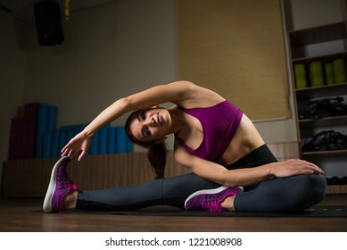 Sporty girl doing stretching on the mat in the fitness hall.