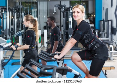 Sporty girl dressed special EMS vests training in busy gym