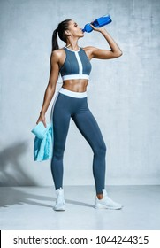 Sporty girl drinking water after workout. Photo of latin fitness girl on grey background. Healthy lifestyle
