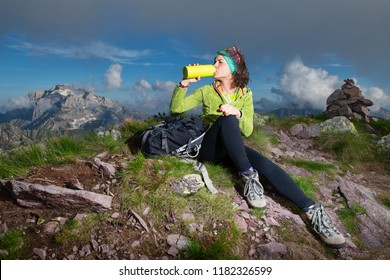 A sporty girl drinks from the water bottle after having conquered the top of a mountain.
