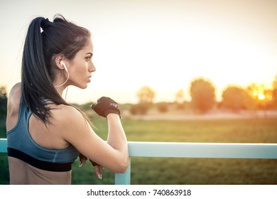 Sporty girl with earphones listening music and enjoying the view outdoors at sunset.
