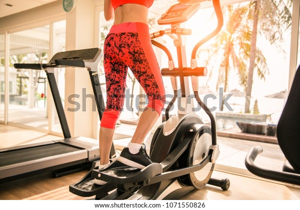 Sporty girl exercise on elliptical cross trainer at gym