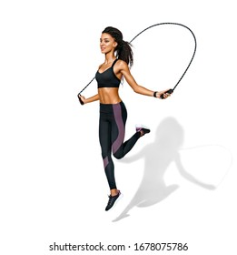 Sporty girl exercising with skipping rope. Photo of african american girl in black sportswear on white background. Dynamic movement. Full length. Sports and healthy lifestyle