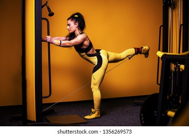 Sporty girl in the gym demonstrates the exercise of hip crossover