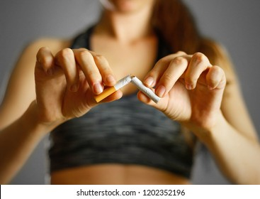 Sporty girl holding a broken cigarette in her hand. Close up. Isolated background.