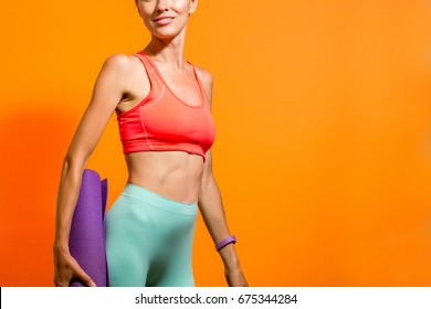 Sporty girl holding yoga mat wearing pants and bra over vibrant orange background. Fashion, sport and healthy lifestyle concept