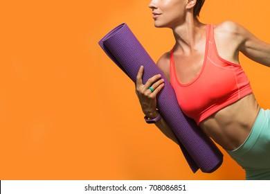 Sporty girl holding yoga mat doing asana over bright orange background