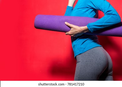 Sporty girl holding yoga mat wearing workout clothing over vibrant red background. Fashion, sport and healthy lifestyle concept