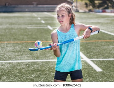 Sporty girl hopping a hockey ball on her hockey stick.