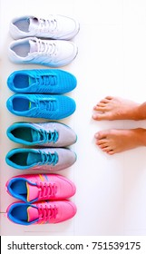 A sporty girl in jeans chooses which sneakers to go for training. Several pairs of sports shoes and legs.