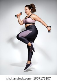 Sporty girl jumping with dumbbells. Photo of model with curvy figure in fashionable sportswear on grey background. Dynamic movement. Side view. Sports motivation and healthy lifestyle