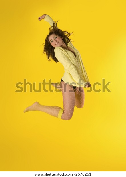 Sporty girl jumping on yellow
