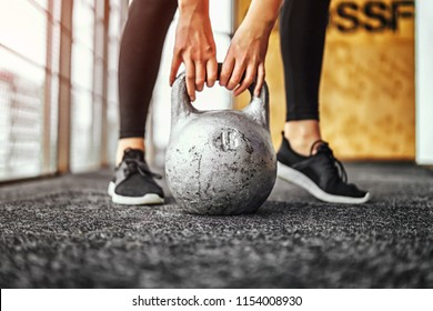 Sporty girl lifting kettlebell from the floor in the gym