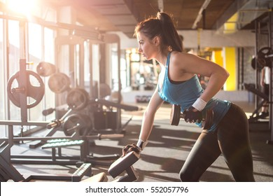 Sporty girl lifting weights in gym.