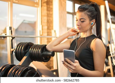 Sporty girl with listening to music on her smartphone at the gym.