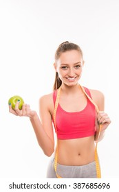 Sporty girl with measuring tape and green apple