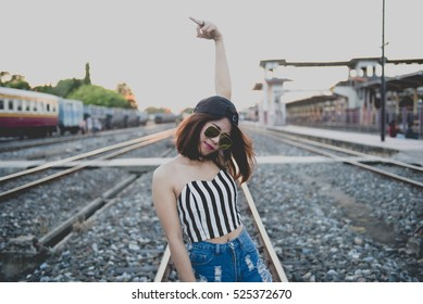 Sporty girl in mini denim shorts with fit ass show middle finger,fuck you on your head on the railway. Outdoor lifestyle portrait, concept of brutal, rebel, punk, furious, indecent,beautiful thai girl