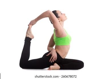 Sporty girl on white background doing back bend eka pada radjakapotasana (one-legged King Pigeon yoga Pose), asana for stretching neck, shoulders, chest, abdomen, groin, thighs