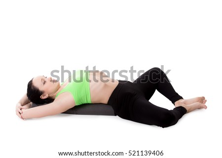 Sporty girl on white background resting in Reclining Bound Angle yoga Pose, Supta Baddha Konasana, restorative, relaxing asana, using bolster. Isolated