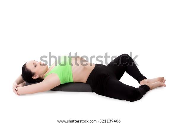 Sporty girl on white background resting in Reclining Bound Angle yoga Pose, Supta Baddha Konasana, restorative, relaxing asana, using bolster. Isolated