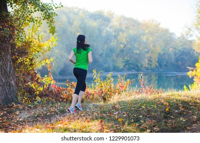 Sporty girl running on the pathway in the forest