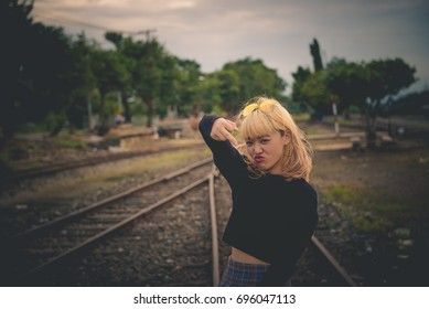Sporty girl show middle finger,fuck you on your head on the railway. Outdoor funny lifestyle portrait, concept of brutal, rebel, punk, furious, indecentThai woman golden hairs,hipster girl