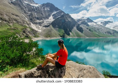 Sporty Girl sitting enjoying beautiful view of mountain lake near Kaprun,Austria.Quiet relaxation outdoors.Wonderful nature landscape,turquoise water,holiday travel scene.Wanderlust happy woman