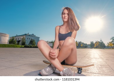 Sporty girl is sitting on skateboard with her bare legs crossed and looking at camera, backlit shot