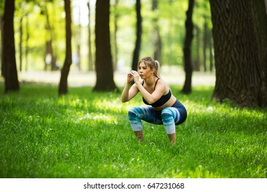 A sporty girl squats in the park on the grass. Fitness and healthy lifestyle.