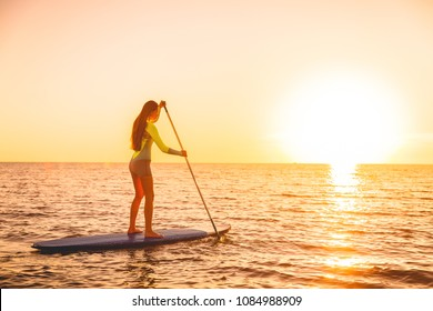 Sporty girl stand up paddle surfing with beautiful sunset or sunrise colors