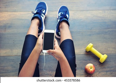 Sporty girl using mobile phone sitting on gym floor.