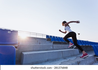 Sporty girl in white shirt running fast to a sunset on a stadium. Side view. Dynamic photo. Young woman in sportswear training on a stadium. Copy space. Sport lifestyle concept