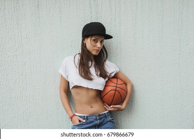 Sporty girl in a white short T-shirt and a black cap is holding a basketball. Portrait of an active young woman outdoors.