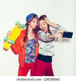 Sporty girlfriends standing having fun together. Beautiful women making selfie. Emotion. Toned.  White background, not isolated
